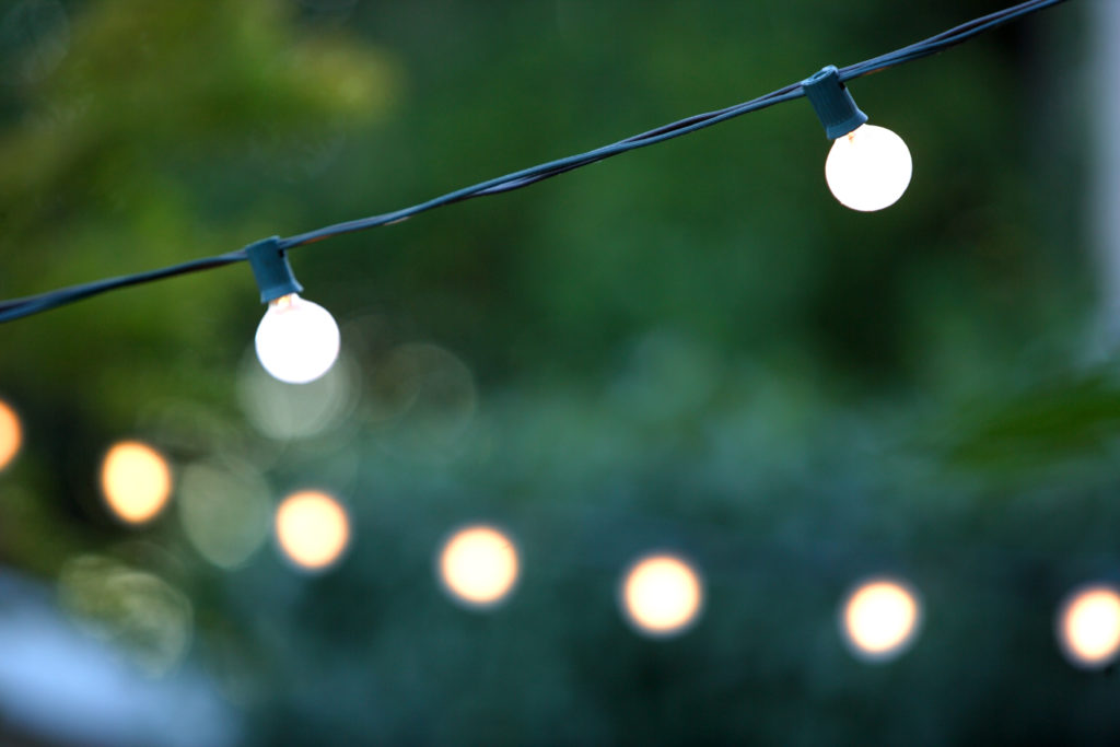 Hanging decorative christmas lights for a back yard party ** Note: Shallow depth of field